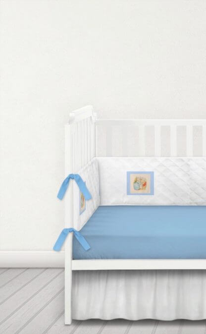 White quilted cot bumper with blue Beatrix Potter patches