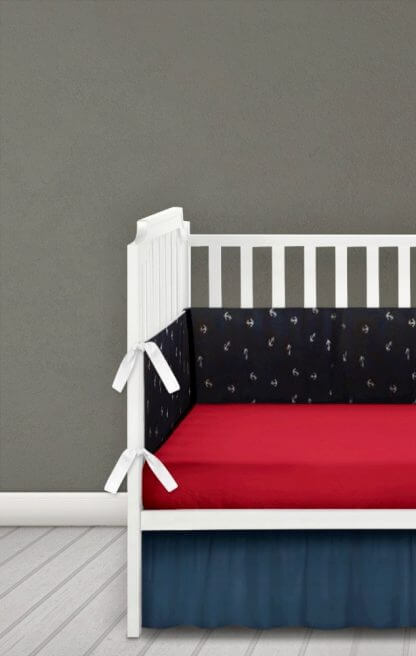 Navy nautical anchors cot bumper with red ties, navy and anchors fabric.