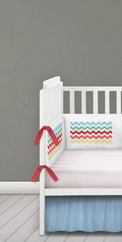 Multi coloured chevron cot bumper with red ties