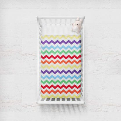 Multi coloured chevron baby quilt with plain white backing