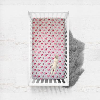 fitted cot sheet with pink and red flowers all over it.
