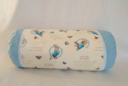 Bolster cushion with Peter Rabbit illustrations in yellow and blue with lace.