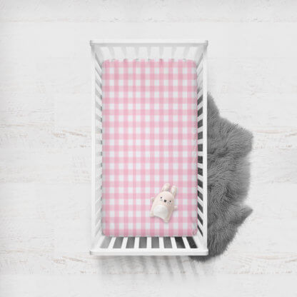 Fitted cot sheet with large pink gingham squares